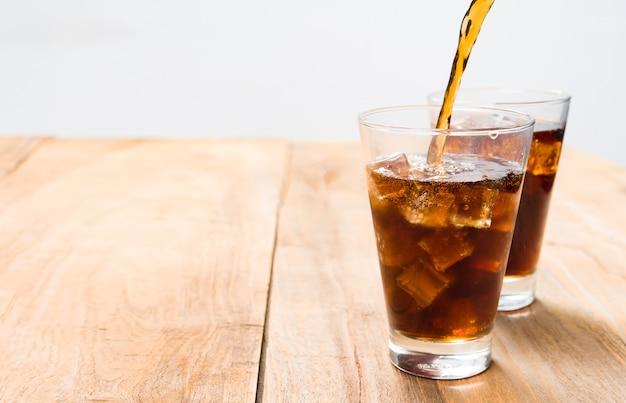 Versando la bevanda rinfrescante di soda in vetro sulla tavola di legno.