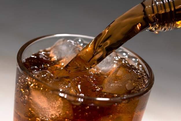 Versare rum o brandy nel bicchiere con ghiaccio