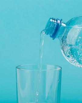 Versare acqua frizzante dalla bottiglia di plastica in vetro