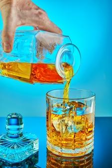 Decanter di cristallo quadrato di versamento con scotch whisky o brandy in un bicchiere tondo di cristallo su uno sfondo blu sfumato con riflessione