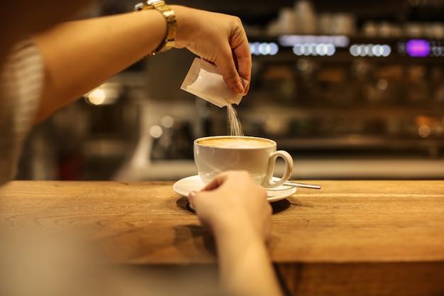 Versare lo zucchero nel caffè