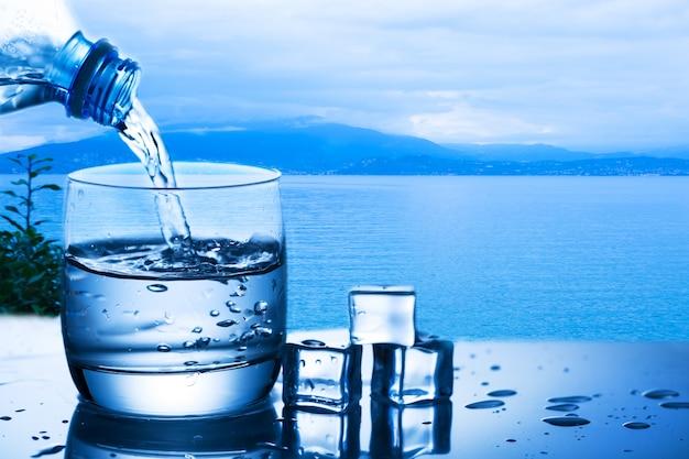 Acqua di versamento dalla bottiglia in un bicchiere contro lo sfondo della natura con il lago e la pianta vicino ai cubetti di ghiaccio
