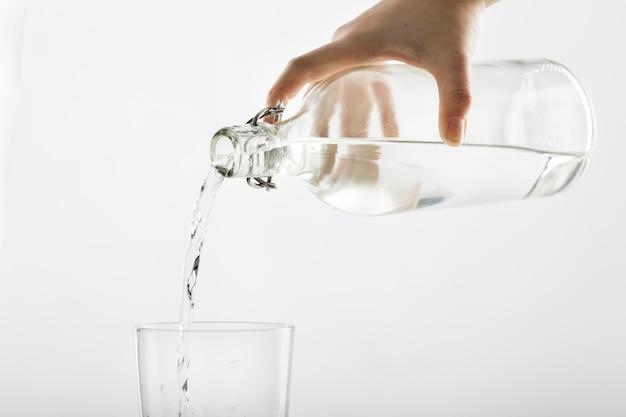 Versare l'acqua dalla bottiglia al bicchiere