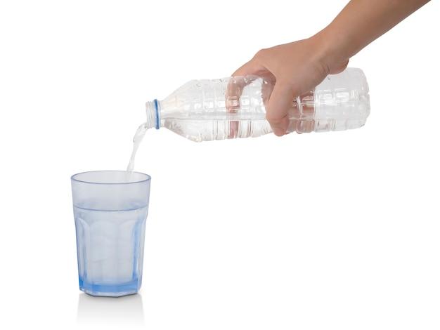 Acqua di versamento dalla bottiglia di plastica in vetro isolato su bianco. tracciato di ritaglio