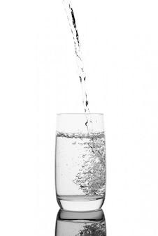 Versare l'acqua in un bicchiere, isolato su una superficie bianca