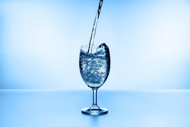 Versare l'acqua nel bicchiere sull'azzurro