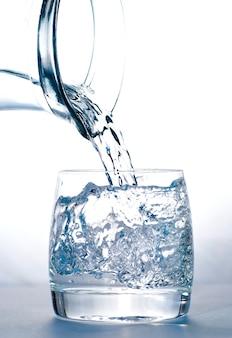 Versare l'acqua nel bicchiere dalla brocca