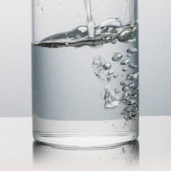 Versare l'acqua in un bicchiere