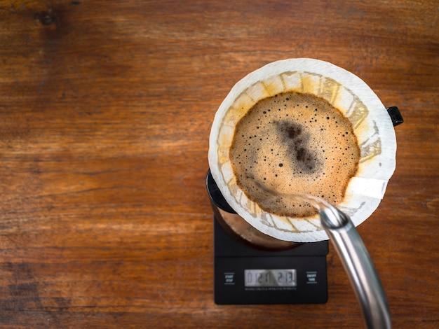 Versare acqua sui fondi di caffè tostato chiaro attraverso il gocciolatore con carta da filtro.