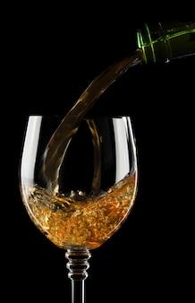 Versare il vino in un bicchiere isolato su sfondo nero