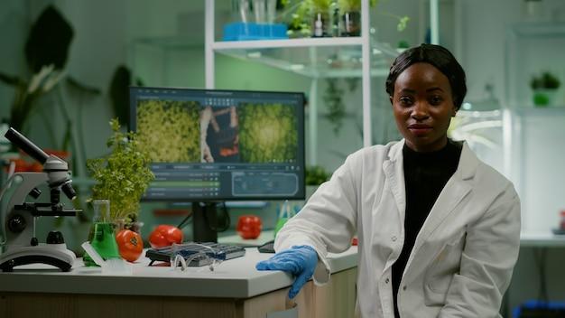 Punto di vista di una donna africana seduta al tavolo della scrivania nel laboratorio farmaceutico durante la riunione di videochiamata online