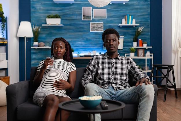 Pov di coppia nera in attesa di un bambino che guarda la tv insieme sul divano del soggiorno. afroamericani che guardano la telecamera e la televisione mentre la donna incinta tiene in mano un bicchiere d'acqua