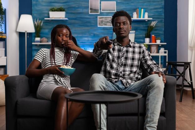 Pov di coppia sposata nera sul divano guardando la televisione e guardando la fotocamera. donna afroamericana che mangia popcorn dalla ciotola mentre l'uomo tiene il telecomando della tv a casa