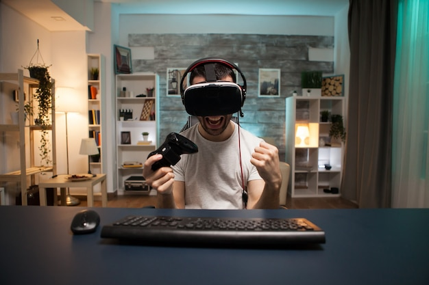 Punto di vista di un giovane eccitato per la sua vittoria sul gioco online indossando occhiali per la realtà virtuale.