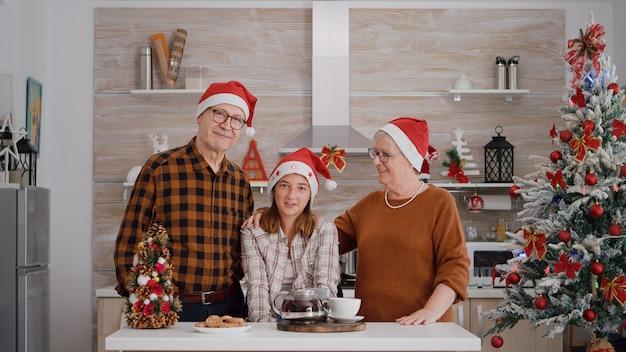 Pov di famiglia che indossa cappelli di babbo natale che saluta gli amici durante la conferenza videochiamata online online