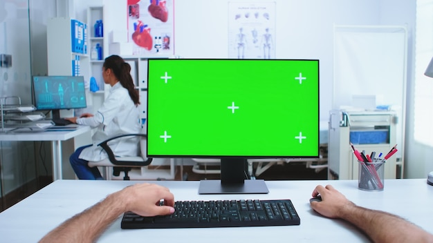 Pov di medico che utilizza computer con spazio di copia disponibile nell'armadietto dell'ospedale e medico in background. medico nell'armadio della clinica desktop funzionante con schermo verde disponibile.