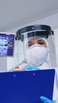 Punto di vista del paziente che riceve cure dentistiche nell'ufficio del dentista con nuova normalità, medico che prende appunti negli appunti prima di esaminare. stomatologo che indossa indumenti di sicurezza contro il coronavirus durante il controllo sanitario