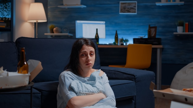 Punto di vista di una donna depressa infelice che piange tenendo un cuscino seduto sul pavimento che soffre di depressione psic...