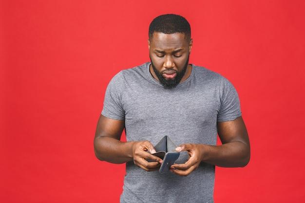 Concetto di crisi di povertà. uomo barbuto giovane afroamericano sconvolto nel portafoglio vuoto della holding casuale