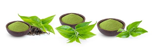 Tè verde matcha in polvere in una ciotola con foglia isolato su superficie bianca
