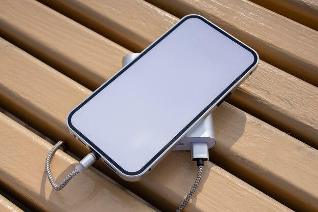 Power bank carica uno smartphone mockup con schermo bianco su una panca di legno nel parco.