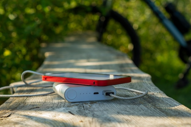 Il power bank carica uno smartphone nella foresta sullo sfondo di una bicicletta.
