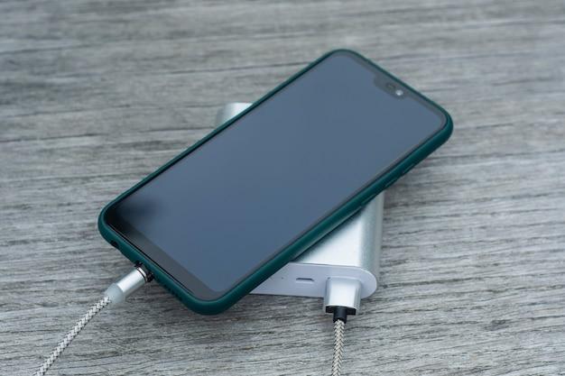 Power bank carica uno smartphone su una panca di legno nel parco.