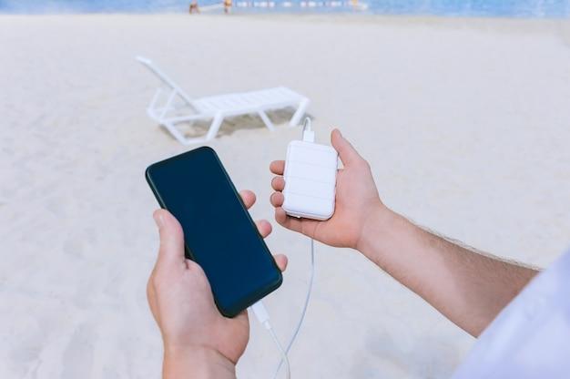 Power bank energy carica il telefono nelle mani di un uomo sulla spiaggia. sullo sfondo di sabbia e un lettino.