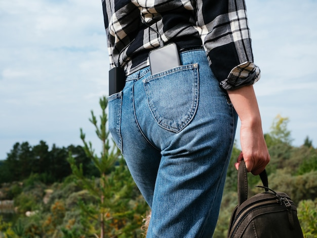Power bank e smartphone sono nelle tasche posteriori dei jeans della ragazza