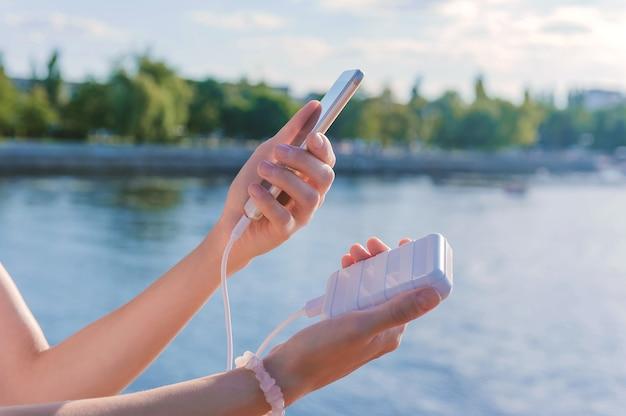 Power bank e uno smartphone nelle mani di una ragazza. sullo sfondo del terrapieno.
