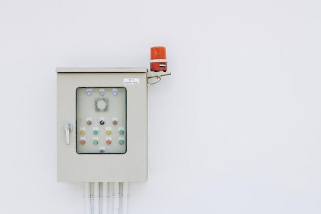 Scatola di alimentazione per l'edilizia industriale interruttori elettrici fusibili pannello interruttori con cicalino di allarme rotante su parete bianca