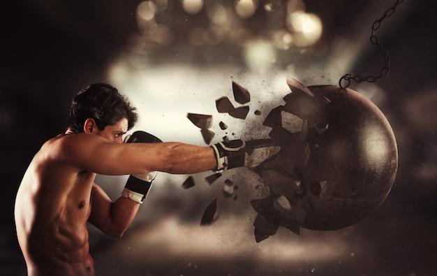 Potenza e determinazione di un giovane pugile muscoloso contro una palla da demolizione