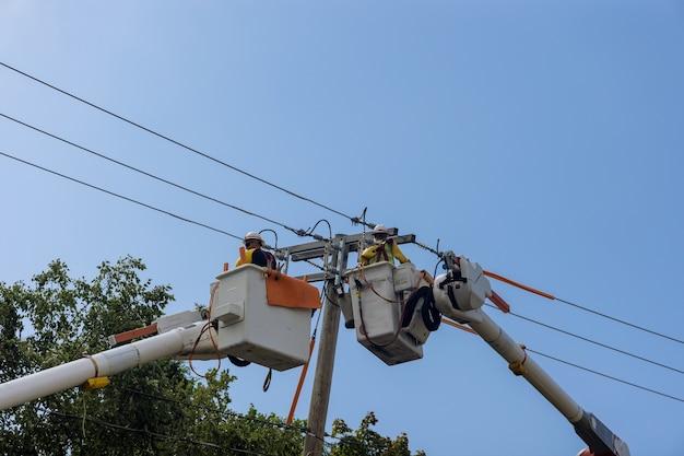 Le linee elettriche di alimentazione supportano gli uomini di servizio che lavorano per gestire i danni dopo l'uragano