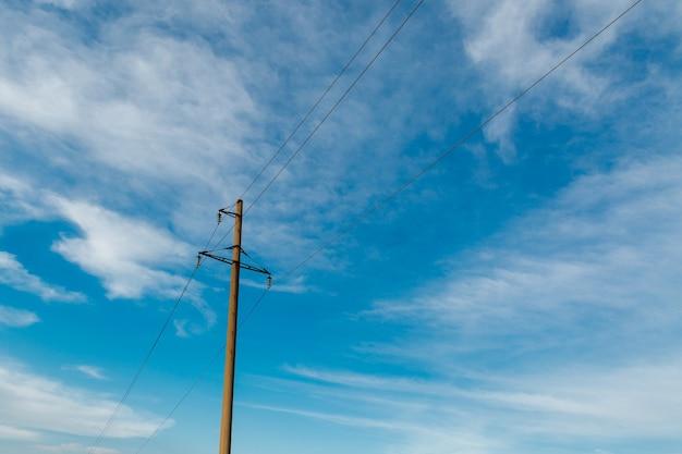 Palo della linea elettrica con cavi elettrici contro un cielo limpido con nuvole bianche, linea di trasmissione elettrica, alimentazione elettrica