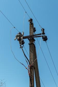 Post di linea elettrica con cavi elettrici contro un cielo limpido con nuvole bianche