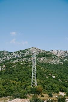 Pilone della linea elettrica sulla superficie della montagna verde