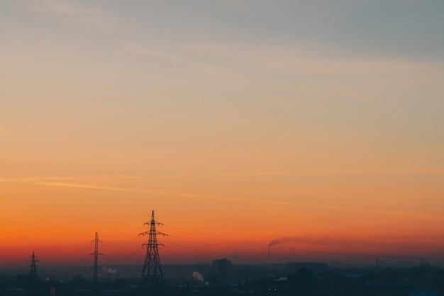 Linee elettriche in città all'alba. siluette delle costruzioni urbane fra smog su alba. cavi di alta tensione sul caldo cielo giallo arancio. industria energetica al tramonto. alimentazione elettrica della città. nebbia sfondo urbano.