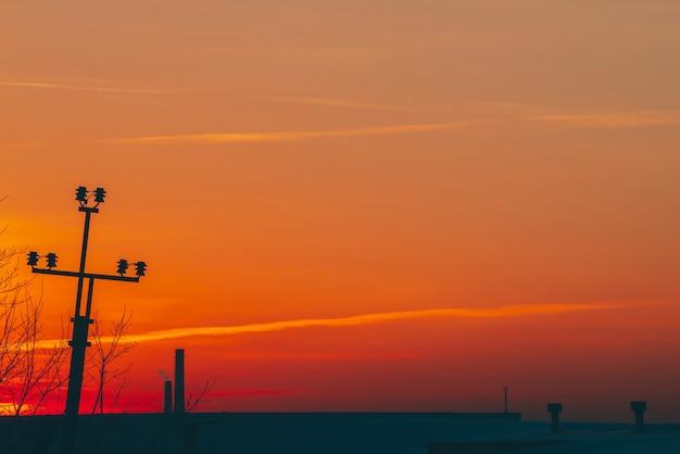Linee elettriche sopra il tetto all'alba. siluette del mucchio con i fili fra smog su alba. cavi ad alta tensione sul caldo cielo giallo arancio. industria energetica al tramonto. alimentazione elettrica della città. nebbia sfondo urbano.
