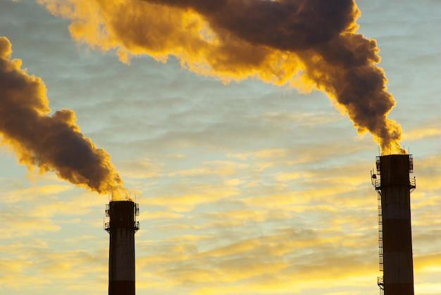 Centrale elettrica con fumo sotto il tramonto
