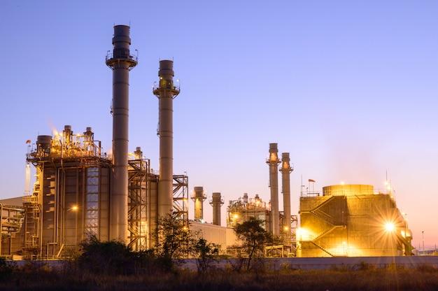 Centrali elettriche e serbatoi di stoccaggio di gas naturale siluetta dell'attrezzatura d'acciaio della raffineria al tramonto