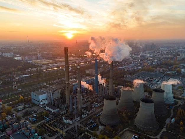 Centrale elettrica con molti tubi e strutture a bucarest al tramonto, molta schiuma, vista dal drone, romania
