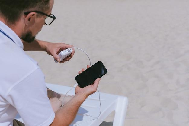 Powerbank carica uno smartphone nelle mani di un ragazzo sulla spiaggia. sullo sfondo di sabbia.