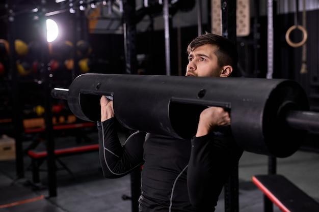 Potente atleta che solleva pesi, utilizzando attrezzature sportive in palestra moder, l'uomo è concentrato sull'allenamento di allenamento sportivo. bel ragazzo in abito sportivo