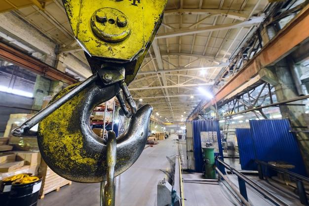 Primo piano potente della gru del gancio. sullo sfondo dell'impianto industriale. sfondo industriale.