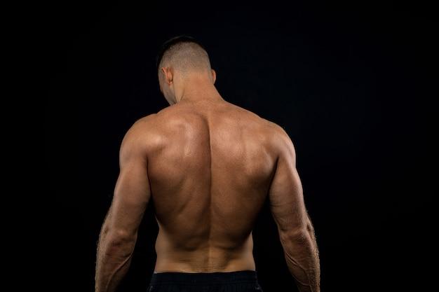 Il potente atleta muscoloso mostra la sua schiena accanto al muro nero