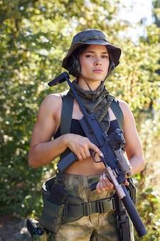 Potente soldato donna sportiva pronto per la battaglia che indossa un'arma militare protettiva