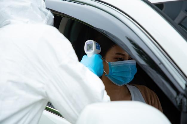 Il team operativo medico dpi controlla la temperatura trova la malattia da virus corona con il concetto drive thru. scansiona l'infezione con la pistola termica. Foto Premium