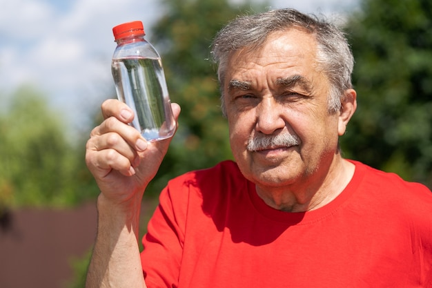 Pritratto di uomo anziano di 70 anni con una bottiglia d'acqua in giardino, giorno d'estate.