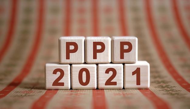 Testo ppp 2021 su cubi di legno su uno sfondo monocromatico con riflessione.