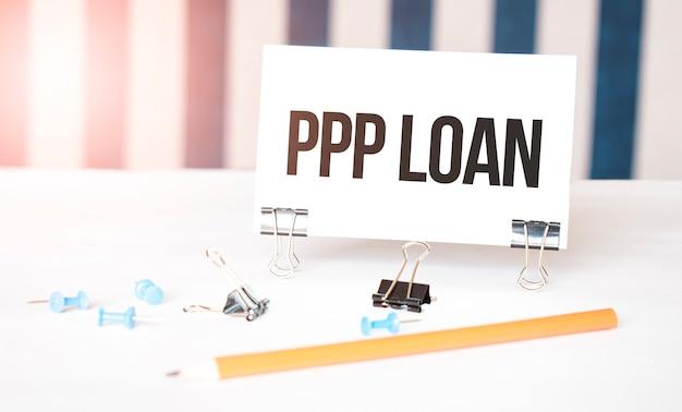 Segno di prestito ppp su carta sulla scrivania bianca con strumenti per ufficio. sfondo blu e bianco